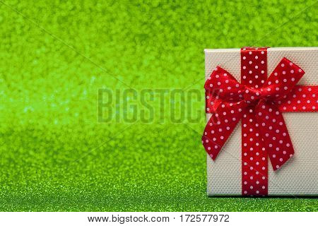 Gift box with red bow on sparkling green background. Bright and festive. close up