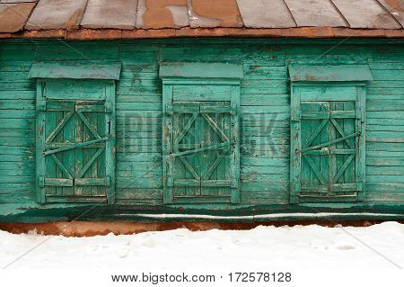 Old poor abandoned country house with three shut windows horizontal