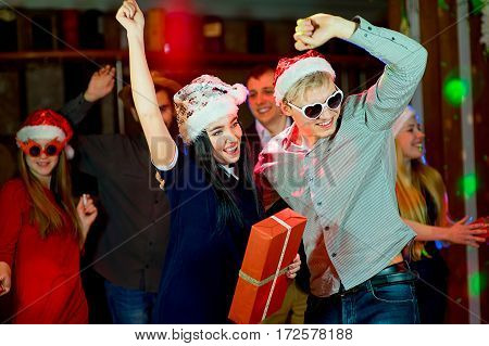 Young peoples Christmas party in the nightclub. Dancing on the dancefloor