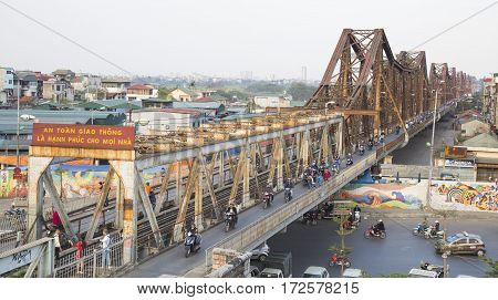 Hanoi, Vietnam - Feb 18, 2017: Vietnamese people riding motorcycles on Long Bien bridge over Hong (Red) river. The bridge was designed by French architect Gustave Eiffel in time French ruled Vietnam.