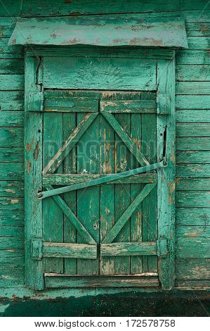 Old wooden country window with closed shutters painted green vertical