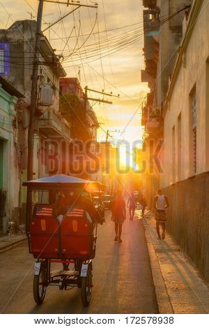 Bicycle with american flags on a street scene in Old Havana illuminated by the sun at sunset