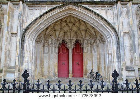 WINCHESTER, UK - FEBRUARY 5, 2017:  Detail of the main entrance to the Cathedral with red doors and arches
