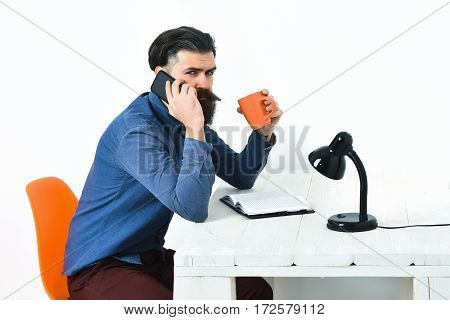 Bearded man long beard. Brutal caucasian unshaven serious hipster with moustache talking by cell phone and orange mug at white vintage wooden table isolated on white background