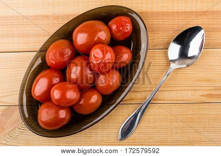 Black Transparent Dish With Red Marinated Tomatoes And Spoon