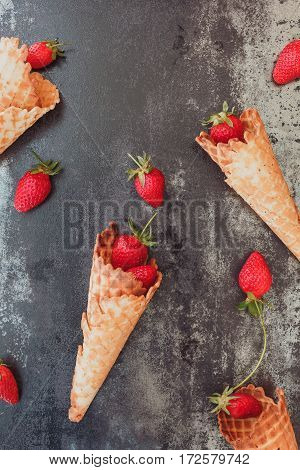 Fruit Cones. Fresh strawberry fruit in ice cream cones, top view, copy space