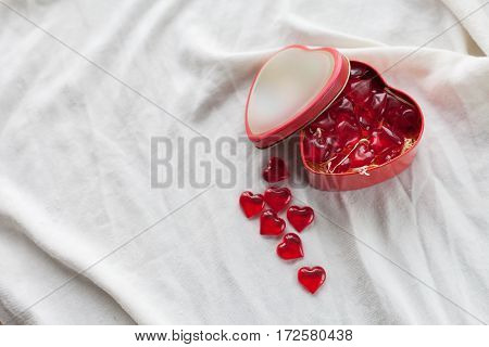 Old box in heart shape on white background on white cloth in box red sweet jelly beans Valentine's day women's day gifts.