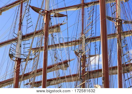 Maritime background with masts, rigging and sails of old sailing ships in front of a blue sky.
