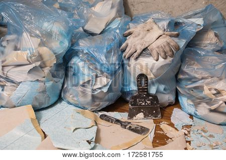 Working gloves. Collect garbage in the garbage bag put things in order. Do makeovers. Putty knife lying on the floor