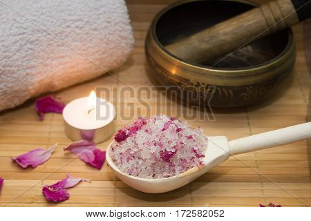 homemade body scrub from sea salt and rose petals and peony Tibetan bowlcandlepink towel on a straw Mat. Spa concept