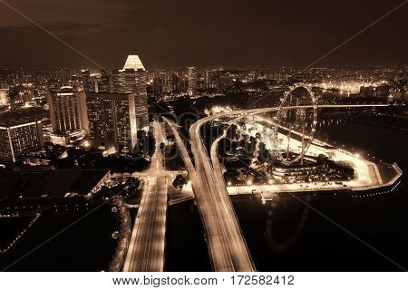 Singapore rooftop view with highway at night and urban skyscrapers.
