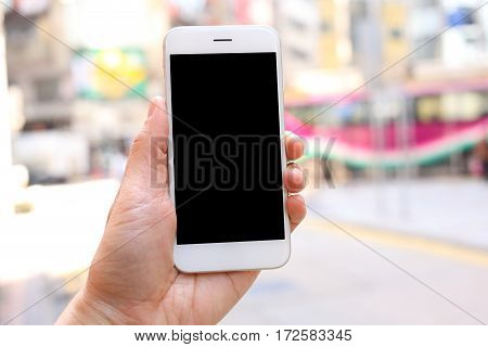 Hand holding mockup smartphone with city street background