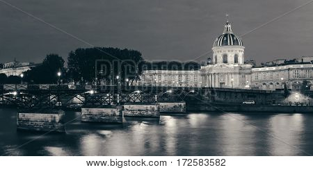 River Seine with Pont des Arts and Institut de France panorama at night in Paris, France.