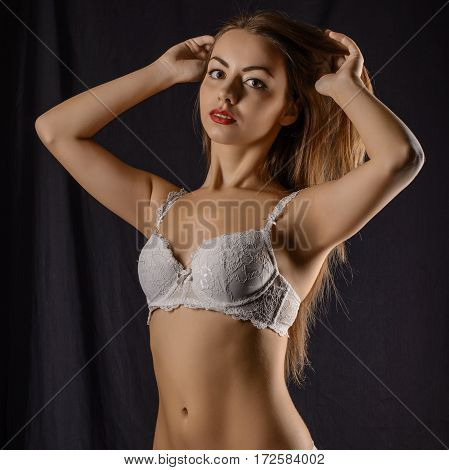 Portrait of an attractive young woman in a white bra.