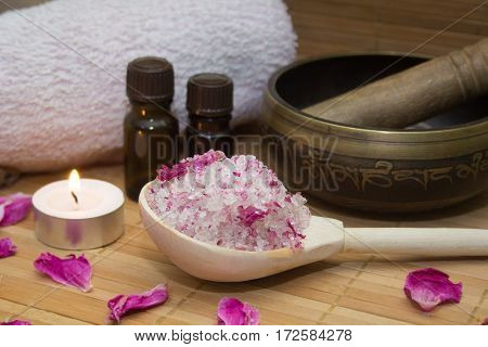 homemade body scrub from sea salt and rose petals and peony Tibetan bowlcandlepink towel and aroma oil on a straw Mat. Spa concept