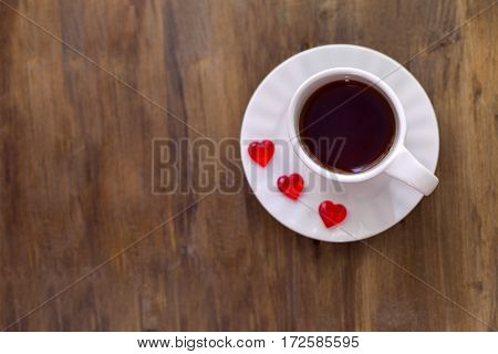 A Cup of tea or coffee with jelly in the shape of heart on wooden background.