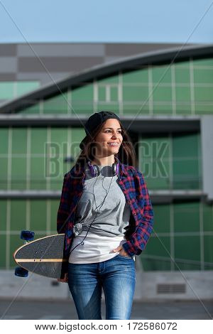 Shot of smiling female in trendy clothes holding skateboard while being outside.