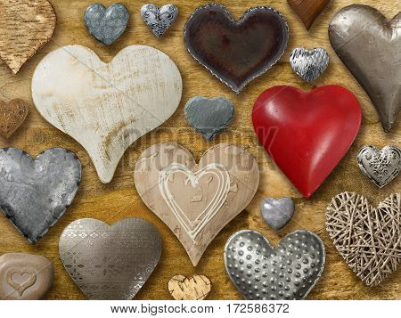 Photos of many heart-shaped things made of stone metal and wood on wood background.