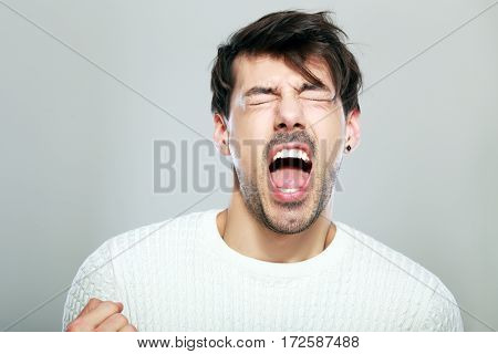 crazy man yelling with his eyes closes studio portrait