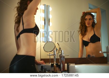 Young woman looking herself in the mirror on bathroom