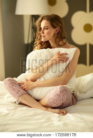 Young woman holding a pillow while sitting on her bed