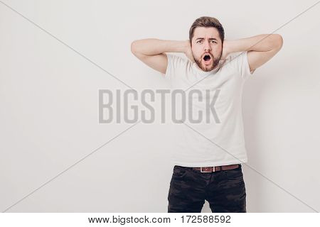 indignant young man with dark hair and the beard in white t-shirt shouts in front of a white wall. soft light
