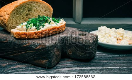 Farmer cheese, bran bread loaf and sandwich with green onion and dill
