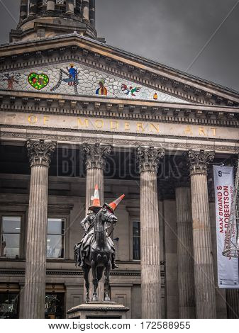 GLASGOW, SCOTLAND - 29 JAN 2017: Exterior of the Gallery of Modern Art with a statue of the Duke of Wellington, who nearly always has a traffic cone on his head as a testament to Scottish humour