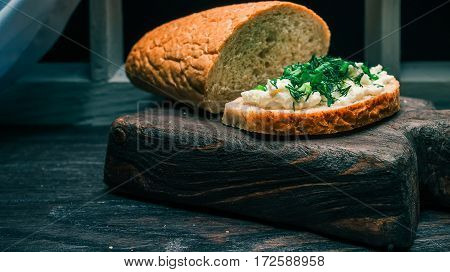 Bran bread loaf and sandwich with cottage cheese and green potherbs