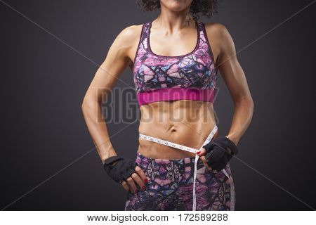 Fit young woman measuring her waist by measure tape