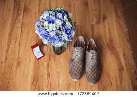 Gray man's shoes on the floor. Men's style fashion. Charges groom. Wedding bouquet of blue and white flowers wedding rings lie on a wooden background.
