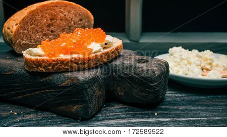 Farmer cheese, bran bread loaf and sandwich with salmon roe