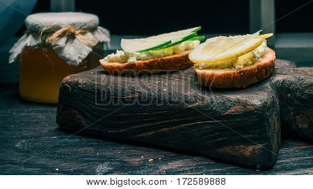 Sandwiches of bran bread with cottage cheese with apple and lemon toppings. Honey on the background