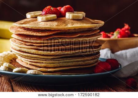 Pancake Stack with Strawberry and Banana Slices.