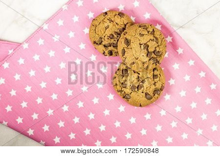 A photo of crunchy chocolate chips cookies, shot from above on a pink textile napkin, with copy space