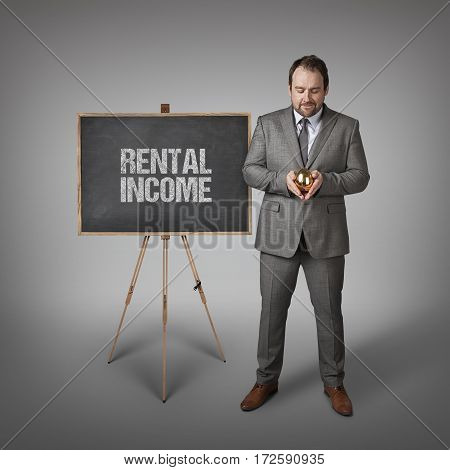 Rental income text on  blackboard with businessman and golden egg