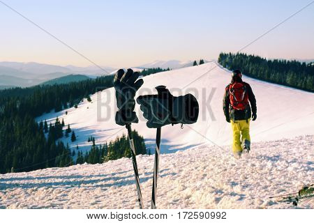 Ski poles gloves and skier that goes uphill on the background of the Carpathian Mountains Bukovel