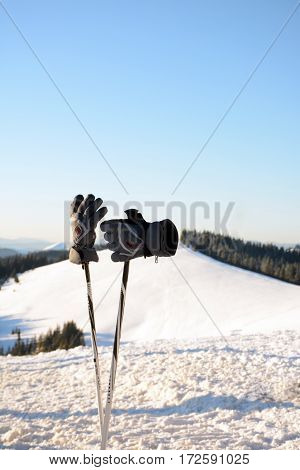 Ski poles and gloves on the background of the Carpathian Mountains Bukovel