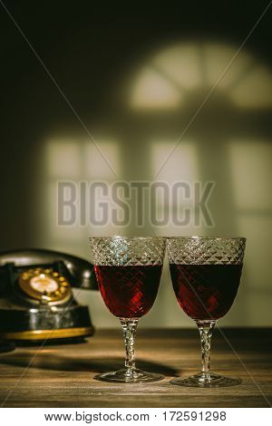 Two antique glasses filled with claret.  Vintage telephone in the background