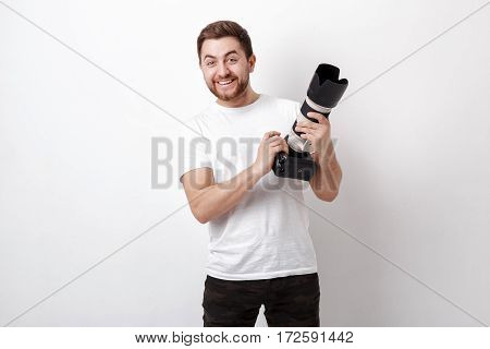 young smilling professional photographer in white  t-shirt use digital camera with a long lens
