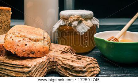 Bran bread loaf, cut toasts, milk and honey on rustic wood board