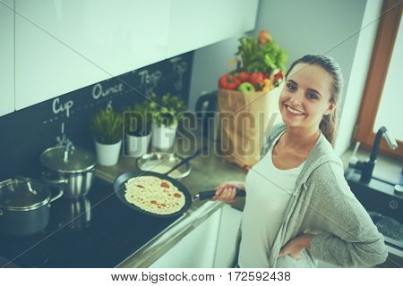 Young woman cooking pancakes at kitchen standing near stove