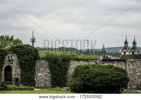 Green park with wall with skyline Church and radio tower in Krakow Poland