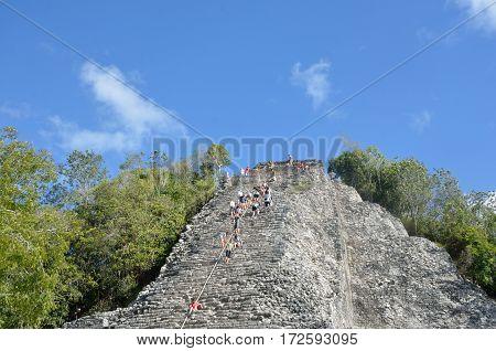 Coba Mexico - January 19 2017: Tourists climbing stone Temple at Coba Yucatan Mexico
