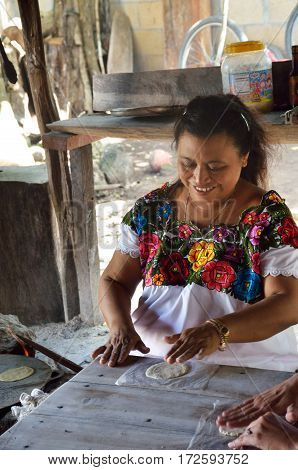 Coba Mexico - January 19 2017: Woman making Tortillas in traditional way