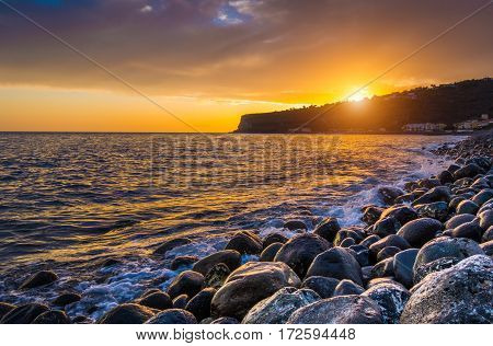 Panorama view of amazing ocean scenery with rocks on a beach in beautiful golden evening light at sunset with blue sky clouds and sunlight lens flare effect in the background in summer