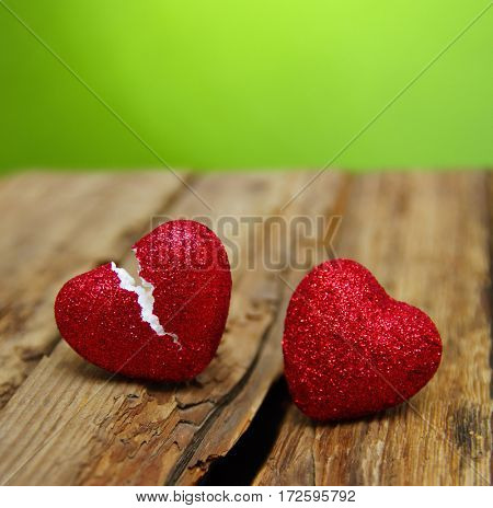 love concept. Broken heart cheating on wood and green  background.