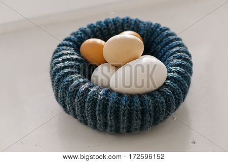chicken eggs in a nest of blue like a hat