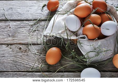 Fresh chicken brown and white eggs on linen napkin with hay at rustic wood table. Top view. Rural still life, natural healthy food and organic farming concept.