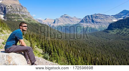 panorama of young man enjoying gorgeous mountain and valley view in glacier national park montana state usa